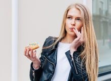 Beautiful young sexy woman eating a donut, licking her fingers taking pleasure a European city street. Outdoor. Warm color. Stock Photos