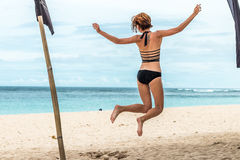 Beautiful young woman jumping for joy on the beach of tropical Bali island, Indonesia. Sunny summer day scene. Beautiful young woman jumping for joy on the royalty free stock photography