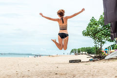 Beautiful young woman jumping for joy on the beach of tropical Bali island, Indonesia. Sunny summer day scene. Beautiful young woman jumping for joy on the stock images
