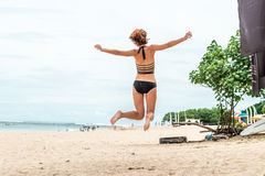 Beautiful young woman jumping for joy on the beach of tropical Bali island, Indonesia. Sunny summer day scene. Beautiful young woman jumping for joy on the royalty free stock photos