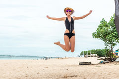 Beautiful young sexy woman jumping for joy on the beach of tropical Bali island, Indonesia. Sunny summer day scene. Royalty Free Stock Photos