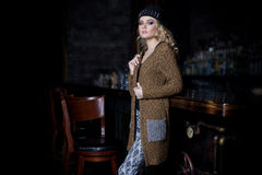 Beautiful young sexy woman with long blond hair, bright make-up Smokey Eyes wearing a sweater next to a dresser and a bar with a c. Atalog of clothing collection Royalty Free Stock Photo