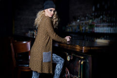Beautiful young sexy woman with long blond hair, bright make-up Smokey Eyes wearing a sweater next to a dresser and a bar with a c. Atalog of clothing collection Royalty Free Stock Photography
