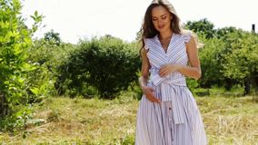 Beautiful young woman long hair bright makeup nature background landscape dry spike grass and apple trees garden summer model. Wear in light white cotton dress stock video footage