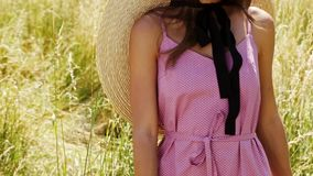 Beautiful young woman long hair bright makeup nature background landscape dry spike grass and trees garden summer model dress. Ed in cotton dress accessory straw stock footage