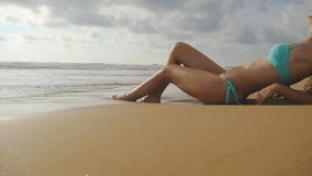 Beautiful young sexy woman lying on golden sand on sea beach and relaxing during summer vacation travel. Ocean waves stock video