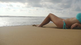 Beautiful young woman lying on golden sand on sea beach and relaxing during summer vacation travel. Ocean waves stock video footage