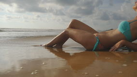 Beautiful young woman lying on golden sand on sea beach and relaxing during summer vacation travel. Ocean waves stock footage