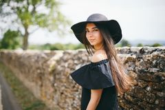 Beautiful young woman model of brunette with dark skin in black dress and hat with fields, fashionably dressed standing in Fr royalty free stock images
