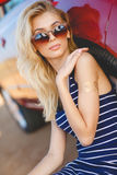 Beautiful young woman near car outdoor. Stylish blonde with long hair in sunglasses,dressed in a dark blue striped sleeveless dress,posing outdoors in the summer stock image