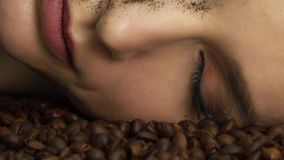 Beautiful young woman portrait bright makeup decorative cosmetics face care lies on roasted coffee beans aromatic scent wraps stock video footage