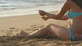 Beautiful young sexy woman sitting on golden sand on sea beach and relaxing during summer vacation travel. Girl playing. With sand on ocean coast. Slow motion stock footage