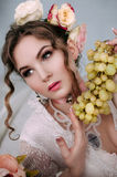 Beautiful young woman sitting on white bed and eating grapes, wearing white lace dress, room decorated with flowers. Perfect Stock Images