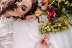 Beautiful young woman sitting on white bed and eating grapes, wearing white lace dress, room decorated with flowers. Perfect Royalty Free Stock Photos