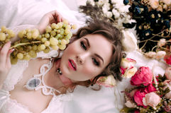 Beautiful young woman sitting on white bed and eating grapes, wearing white lace dress, room decorated with flowers. Perfect Stock Photography