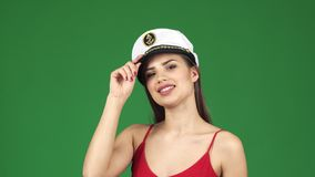 Beautiful young woman smiling joyfully wearing sailor cap on green screen royalty free stock photography