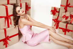 Beautiful young sexy woman thin slim figure evening makeup fashionable stylish coat, clothing collection, brunette, gifts boxes re Royalty Free Stock Photos