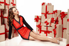 Beautiful young sexy woman thin slim figure evening makeup fashionable stylish coat, clothing collection, brunette, gifts boxes re Royalty Free Stock Image
