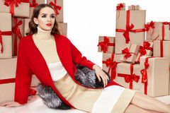 Beautiful young sexy woman thin slim figure evening makeup fashionable stylish coat, clothing collection, brunette, gifts boxes re. Beautiful young sexy woman Royalty Free Stock Image