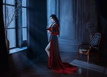 Beautiful young sexy woman vampire in medieval dark castle Red long gothic dress