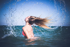 Beautiful young womanhaving fun in refreshing sea water. Bali island. Beautiful young woman enjoying swimming in refreshing sea water. Bali island royalty free stock photos