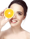 Beautiful young shirtless woman holding piece of orange in front of her eye while standing against white background and Stock Photo