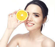 Beautiful young shirtless woman holding piece of orange in front of her eye while standing against white background and Royalty Free Stock Image