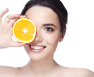 Beautiful young shirtless woman holding piece of orange in front of her eye while standing against white background and Stock Photos