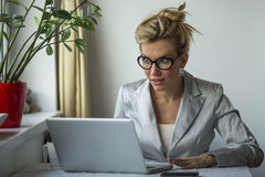Beautiful young shocked business woman sitting in front of laptop computer looking at screen. Emotionally expression face. Royalty Free Stock Photography