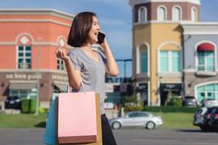 Beautiful young shopaholic Asian woman using smartphone for talking while she walking to buy cosmetics, clothes etc. royalty free stock image