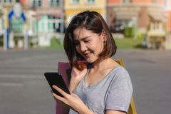 Beautiful young shopaholic Asian woman using smartphone for talking while she walking to buy cosmetics, clothes etc. stock photo