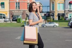 Beautiful young shopaholic Asian woman using smartphone for talking while she walking to buy cosmetics, clothes etc. royalty free stock images