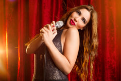 A beautiful young singer performing on stage Stock Image