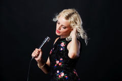Beautiful young singing woman with microphone. Royalty Free Stock Image