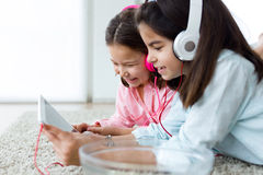 Beautiful young sisters listening to music with digital tablet a Royalty Free Stock Image