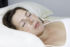 The beautiful young sleeping woman. The beautiful young woman sleeps on white bed Royalty Free Stock Images