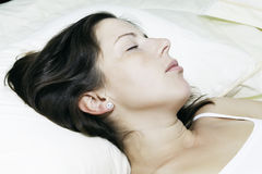 The beautiful young sleeping woman. The beautiful young woman sleeps on white bed Stock Image
