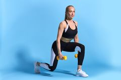 Beautiful young slim fit woman doing lunge exercise with yellow dumbbells royalty free stock image