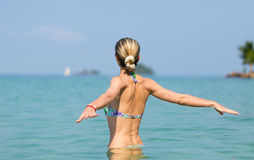 Beautiful young slim girl in the water in the sea, looking away Stock Photos