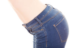 Beautiful young slim topless woman wearing jeans. Showing belly side view isolated on white Stock Images