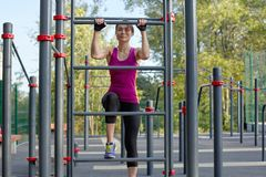 Beautiful young slim woman in bright sportswear climbs up on the ladder at outdoor sportsground. stock photography