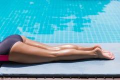 Slim woman legs sunbathe near pool. Beautiful young slim woman legs sunbathe near the swimming pool and the sea, multinational holiday photo Stock Photos