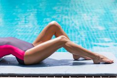 Slim woman legs sunbathe near pool. Beautiful young slim woman legs sunbathe near the swimming pool and the sea, multinational holiday photo Stock Image