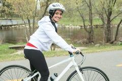 Beautiful young slim woman riding a bicycle Stock Photos