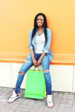 Beautiful young smiling african woman with shopping bags in city Royalty Free Stock Images