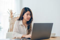 Beautiful young smiling Asian woman working on laptop while at home in office work space. stock photo