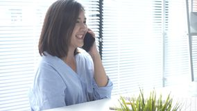 Asian business woman using phone for work in her home office. Enjoying time at home. Beautiful young smiling asian woman working on laptop while sitting in a stock video