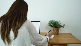 Beautiful young smiling asian woman working on laptop while sitting in a living room at home. stock video footage