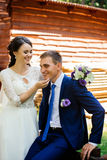 Beautiful young smiling bride holding groom by chin. Couple in love at wedding day Stock Photo