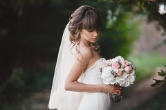 Beautiful young smiling bride holds large wedding bouquet with pink roses. Wedding in rosy and green tones. wedding day royalty free stock images